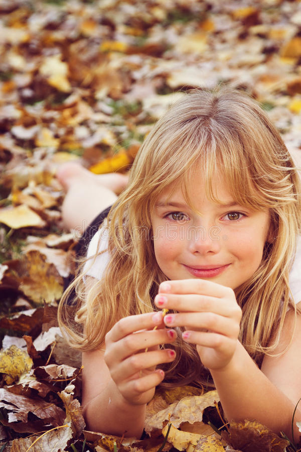 Girl with autumn leaves. A little girl lying in autumn leaves stock image