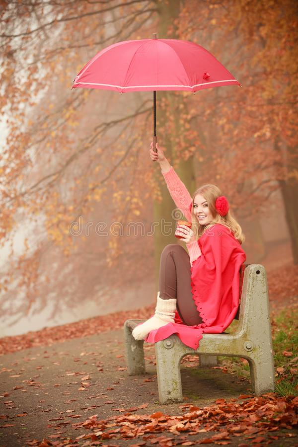 Girl in autumn park enjoying hot drink. Happiness carefree and fall concept. Joyful woman relaxing in autumn park on bench under umbrella enjoying hot drink stock image