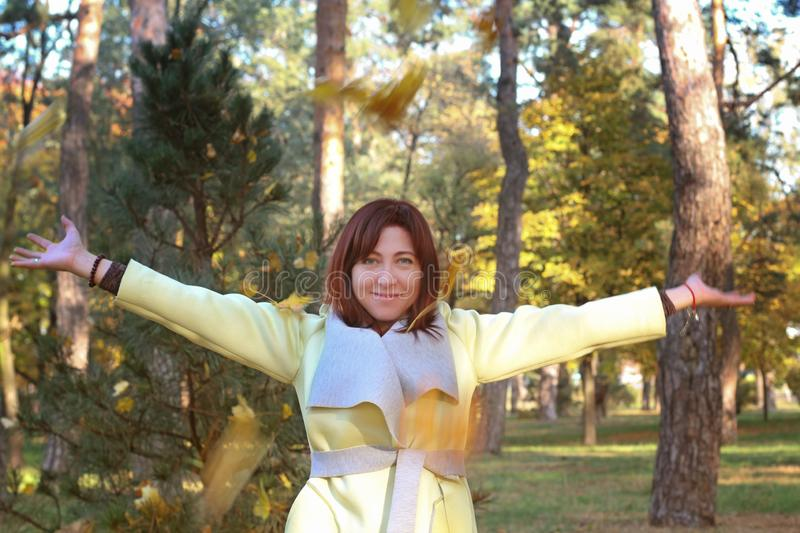 Girl in autumn sits on grass and cheerfully casts up yellow leaves. Life style stock photography