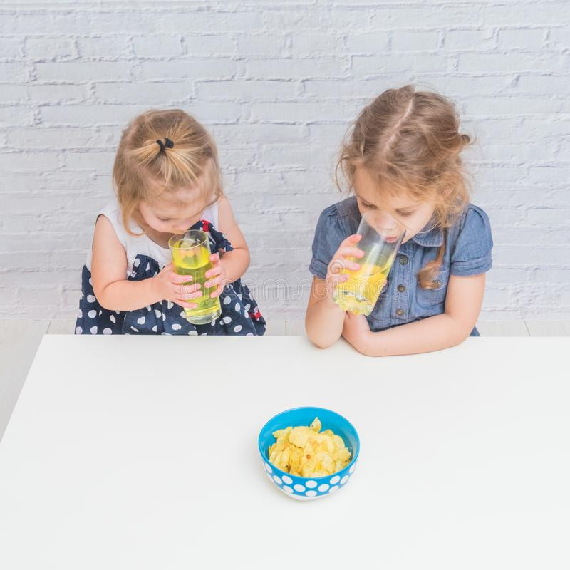 The girl, baby eating potato chips and drinking soda, not health. Girl, baby eating potato chips and drinking soda, not healthy food stock image