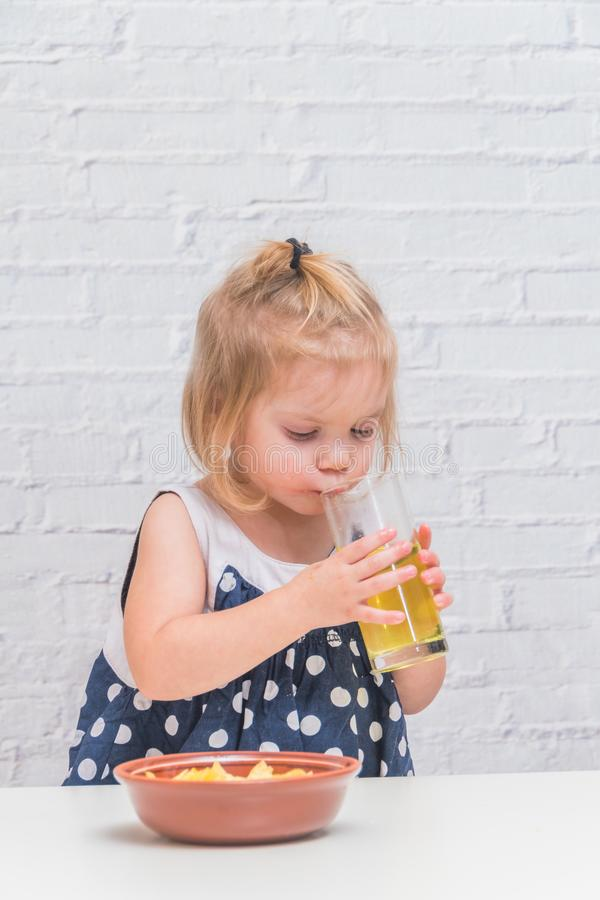 The girl, baby eating potato chips and drinking soda, not health. Girl, baby eating potato chips and drinking soda, not healthy food royalty free stock photo
