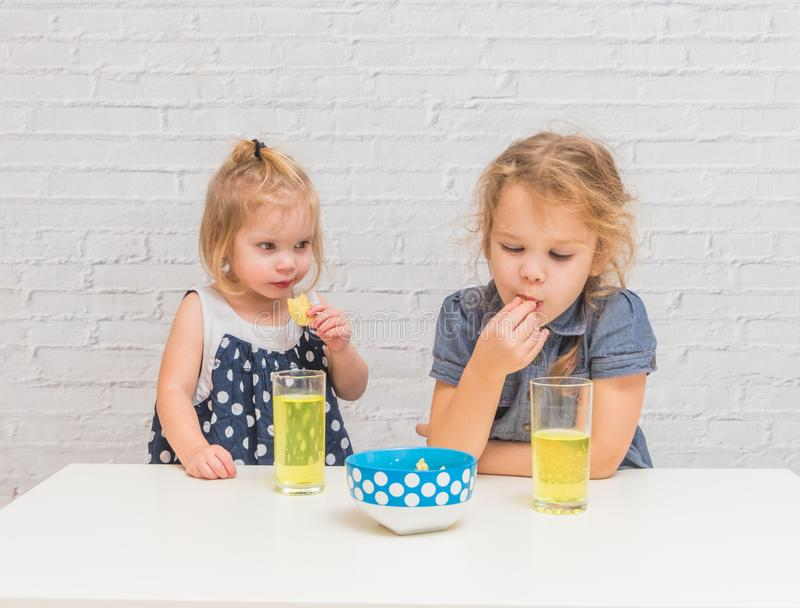 The girl, baby eating potato chips and drinking soda, not health. Girl, baby eating potato chips and drinking soda, not healthy food royalty free stock photos