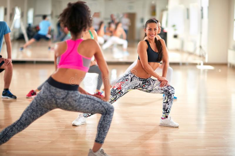 Girl from back show exercises for shaping legs to sport group royalty free stock photos