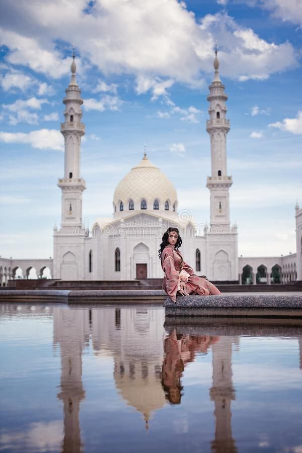 Girl on the background of the mosque stock image