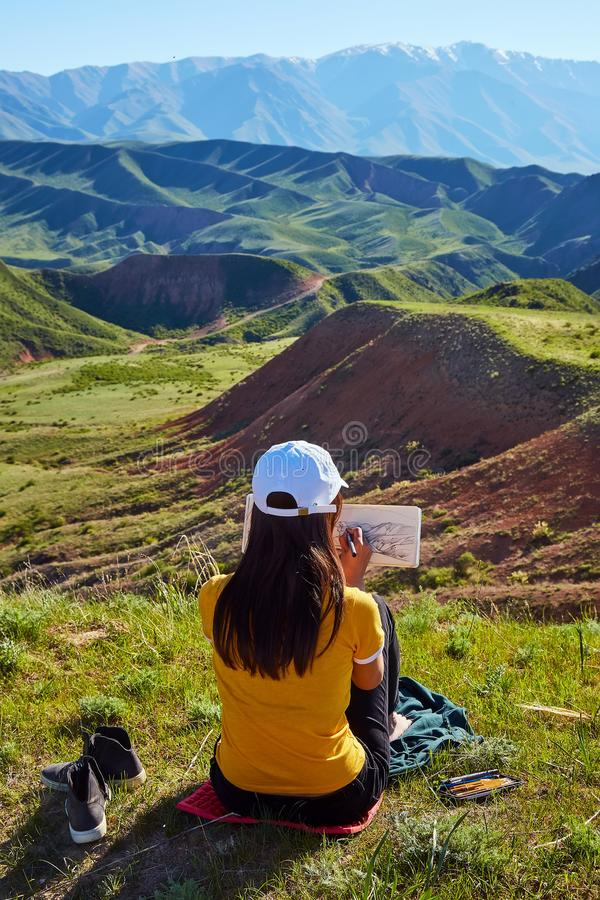 A girl in the background of mountains drawing a landscape. Sits with his back. Painting outdoors. Kazakhstan. Mountain landscape royalty free stock image