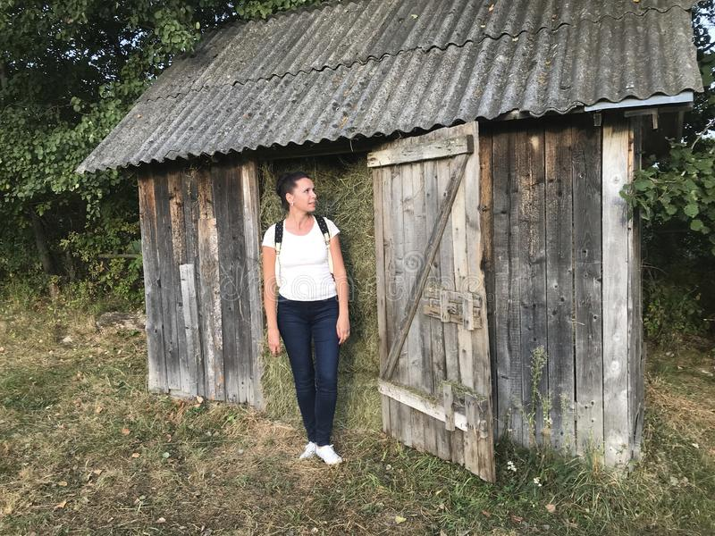 A girl with a backpack behind her. It stands by the wooden shed, which is filled with hay royalty free stock photography