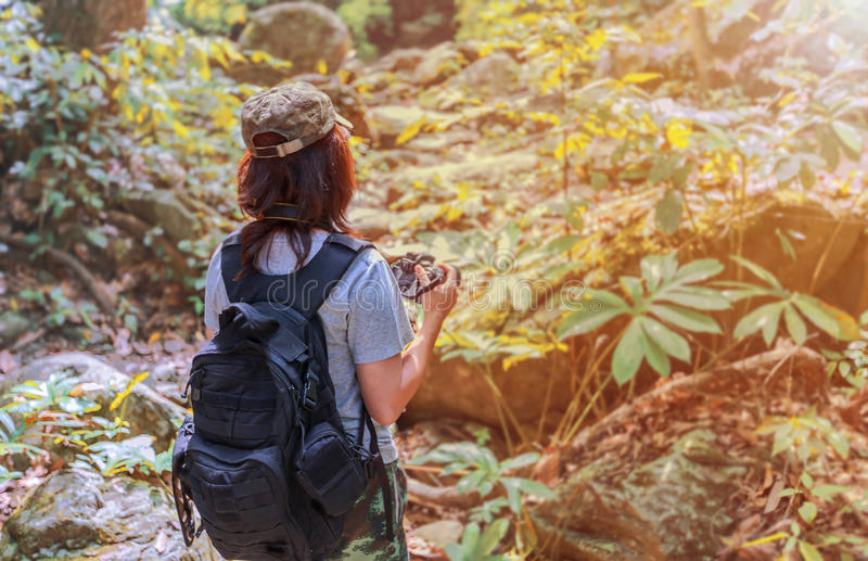 Girl with backpack and camera on trekking trip, standing alone in the trail, enjoying taking photo . Girl with backpack and camera on trekking trip, standing royalty free stock image