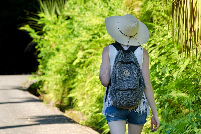 Girl with a backpack and in a hat walking along the road. The palms. Back view royalty free stock images