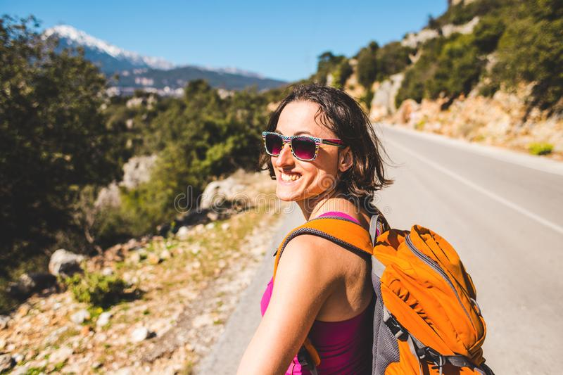 A girl with a backpack is on the road royalty free stock images