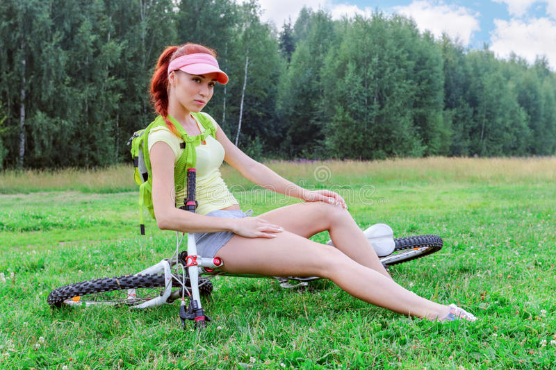 Girl with a backpack sits on a recumbent bike on the gr. Slender girl with a backpack sits on a recumbent bike on the grass on a warm day stock photo