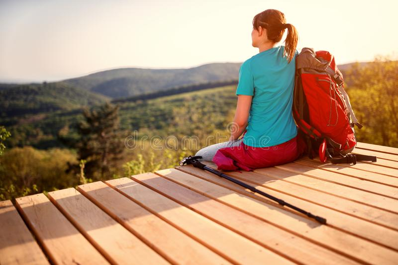 Girl with backpack sitting and looking nature, back view royalty free stock photo