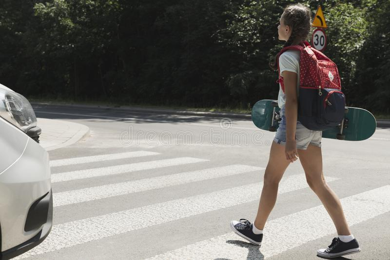 Girl with backpack and skateboard walking. Through pedestrian crossing next to a car stock images