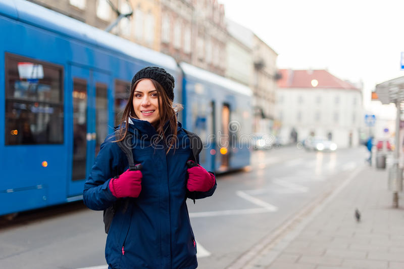 Girl with backpack smiling in the tram station. Tourist woman standing on the street with tram passing by while visiting the city and having a good time royalty free stock images