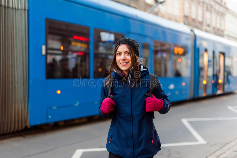 Girl with backpack smiling in the tram station. Tourist woman standing on the street with tram passing by while visiting the city and having a good time royalty free stock image