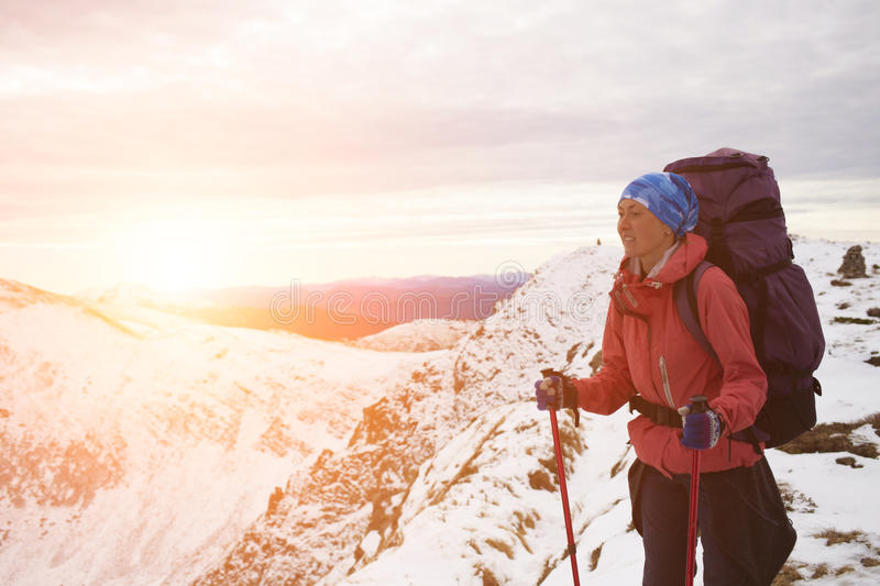 Girl with backpack is traveling in the mountains. The girl with the backpack goes on a mountain trail stock photography