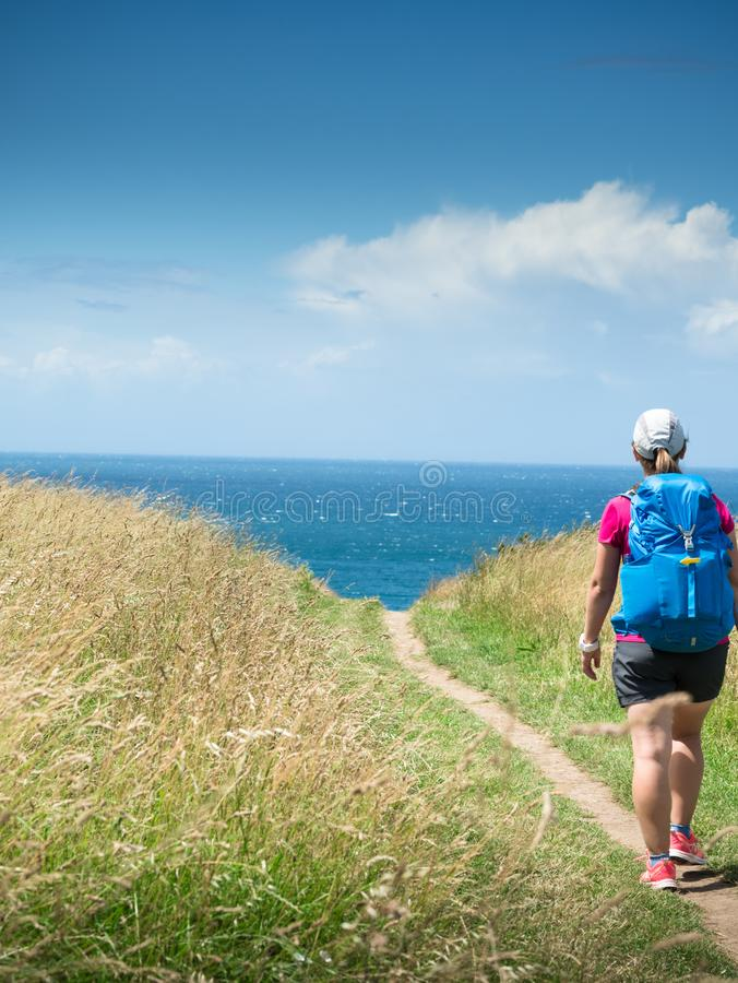 Girl with backpack travels along sea royalty free stock photos