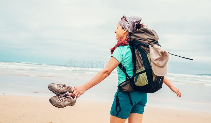 Girl backpacker traveler enjoys with fresh ocean wind stock image