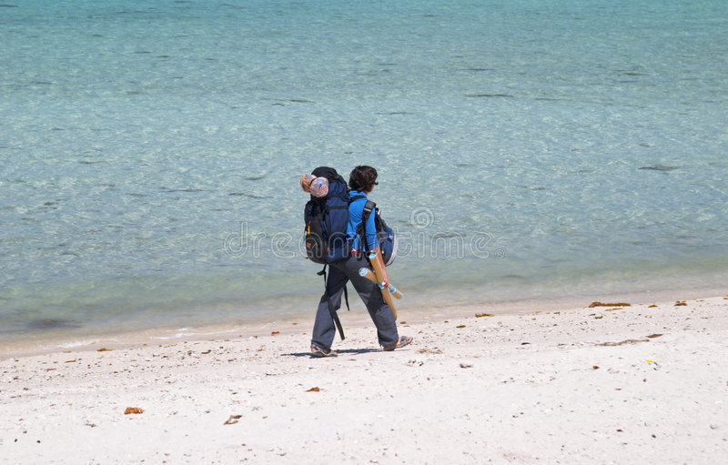 Girl backpacker walking on a beach royalty free stock photography