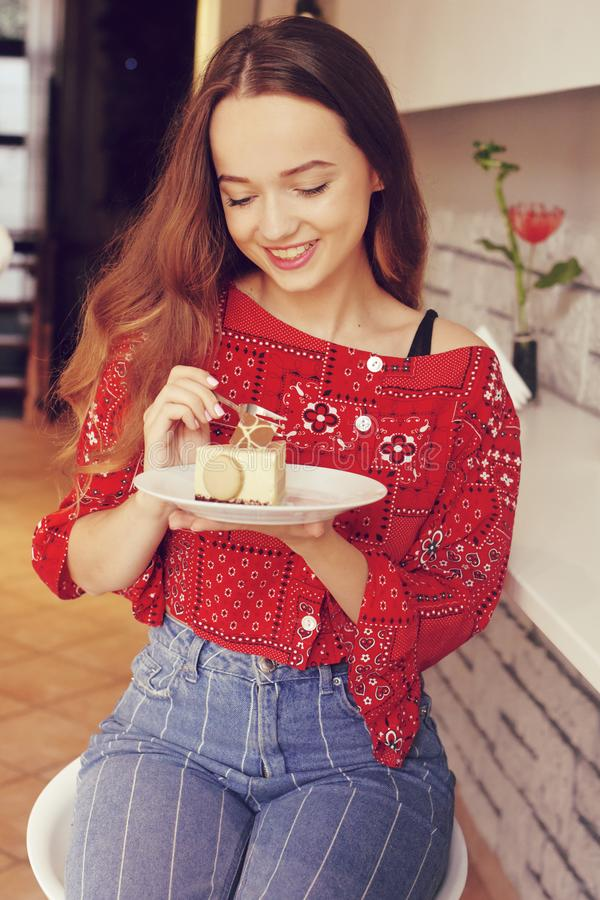The girl in the bakery eats dessert. Beautiful model in a cafe eats sweets and smiling. Beautiful girl in a red sweater. With long hair eats in a restaurant stock photo