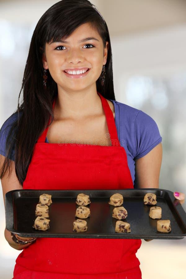 Girl Baking Cookies. Teen girl baking cookies in her kitchen royalty free stock photography