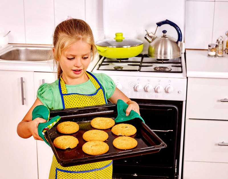 Girl baking cookies in the oven. Little girl kid baking hot cookies in oven royalty free stock images