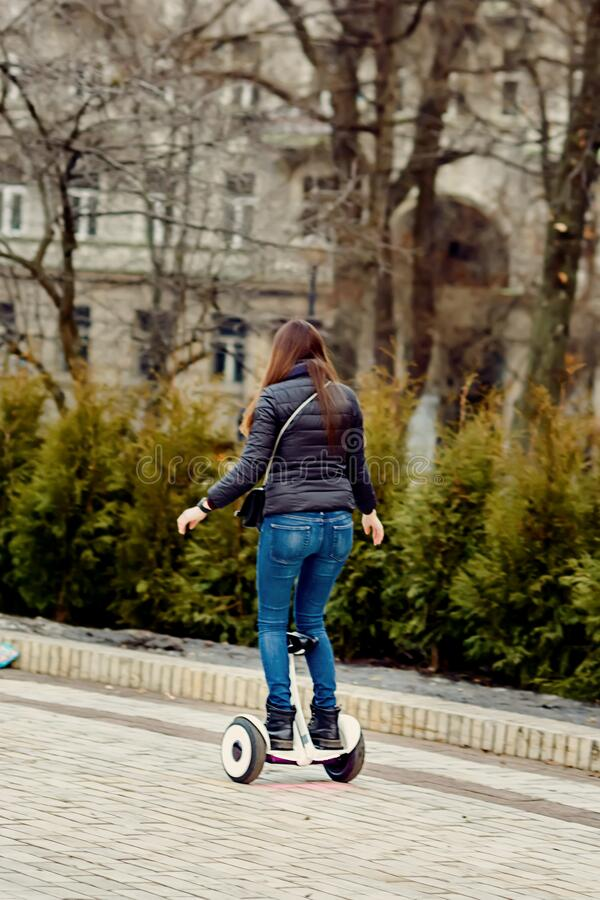 The girl balances on the gyroboard in the park.  stock photo