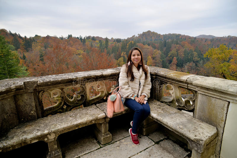 Asian girl at the balcony. Girl at the balcony of the old castle in the forrest royalty free stock photography