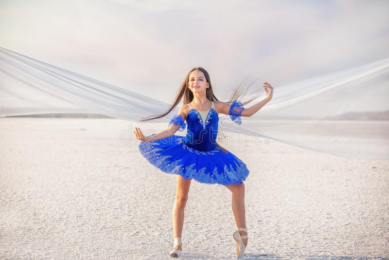 Girl ballerina dancer in a  blue  dress on a snow-white salty dried lake. Fantastic landscape and a girl in  punata and a  blue dr royalty free stock photo