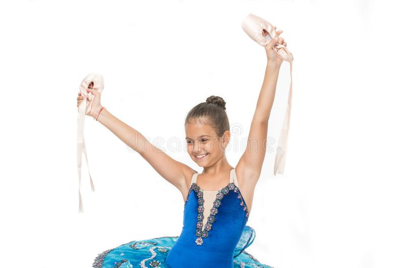 Girl ballerina holds pointe shoes in hand white background. There are many paths to ballet. Child happy holds ballet royalty free stock images
