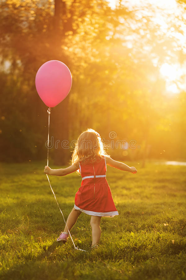 Girl and Balloon. Little girl in a red dress holding a balloon. Happy and carefree childhood stock images