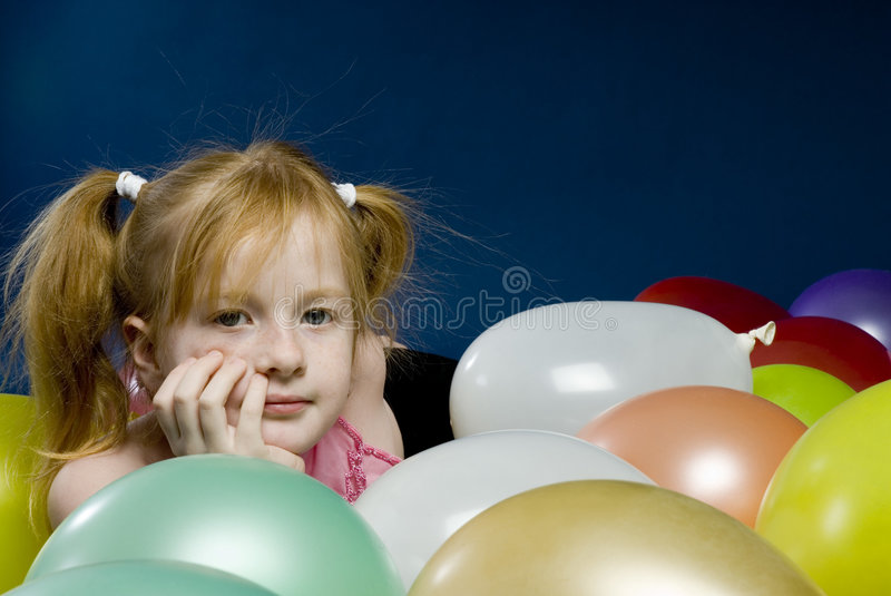 Girl between balloons. Young girl is laying down between balloons stock photography