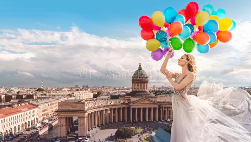 Girl with balloons in a waved dress on the background of St. Petersburg, Russia. Kazan Cathedral. Fashion stock image