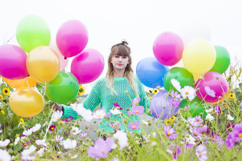 Girl with balloons. Young woman with ballons on a field of flowers stock image