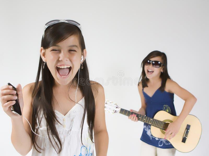 Girl band. Girls band singing and playing on guitar royalty free stock photo