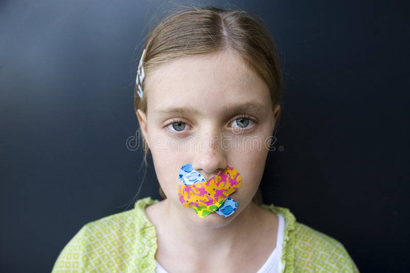 Girl with bandages over her mouth. Keep quiet : portrait of a sad looking girl with colorful bandages over her mouth stock images