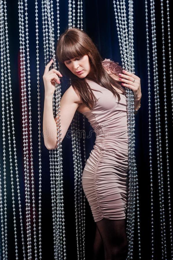 Girl with bangs in a beige dress posing royalty free stock photo