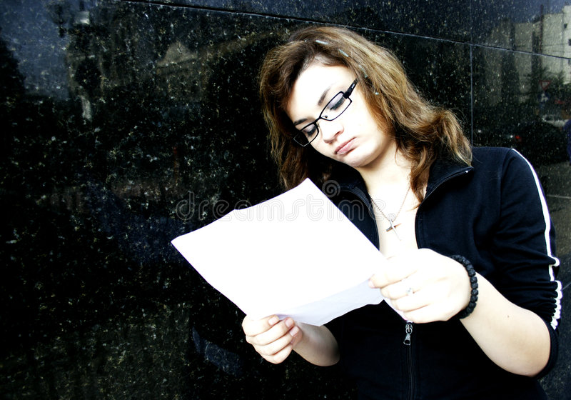 Girl with bank statement. Pretty girl thinking about bank statement stock image
