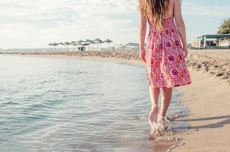 Girl with bare feet walking along the seashore. Concept of summer, travel, beach, vacation and sea. royalty free stock images