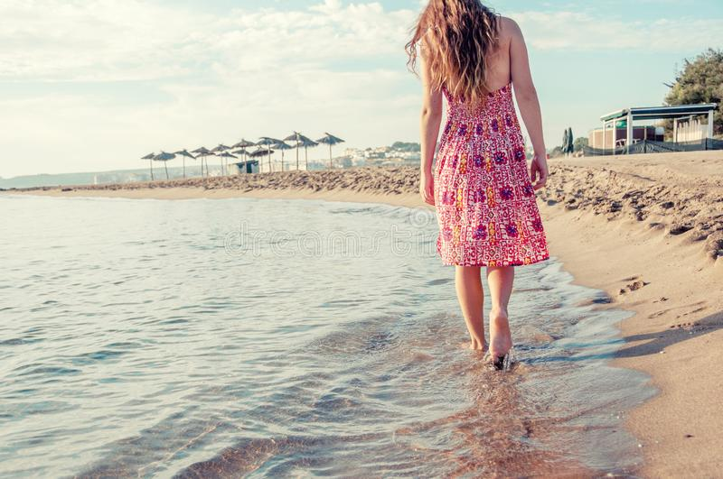 Girl with bare feet walking along the seashore. Concept of summer, travel, beach, vacation and sea. stock images