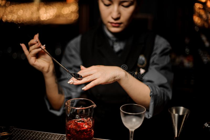 Girl bartender takes a spoon from a cocktail in the measuring glass cup. On the bar counter in the dark blurred background stock photo