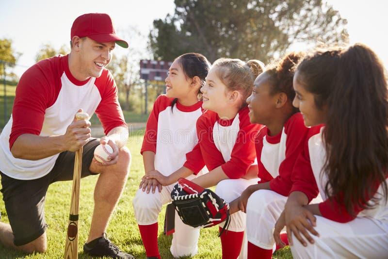 Girl baseball team kneeling in a huddle with their coach stock photos