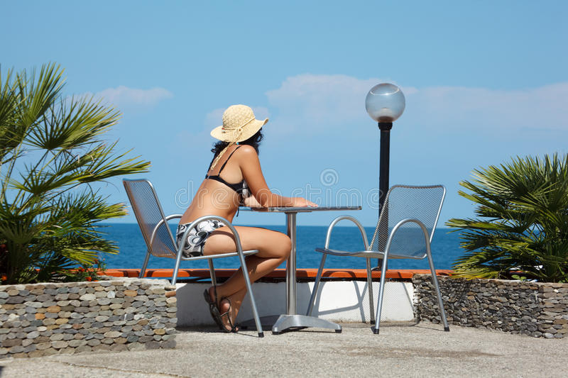 Girl in bathing suit under open sky sits in chair stock photography