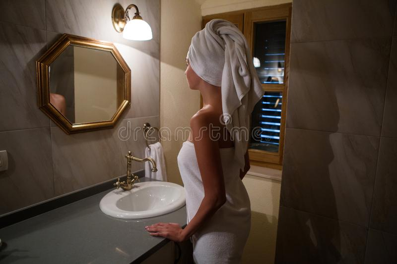 Girl in the Bathrobe in the bathroom standing royalty free stock photography
