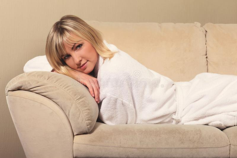 Girl in a bathrobe on the couch. Young girl in a bathrobe on the couch royalty free stock images