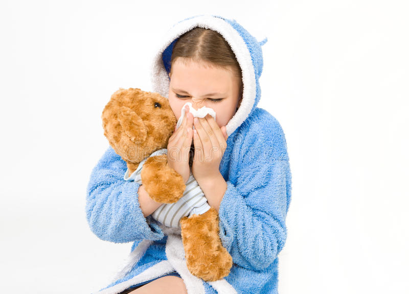 Girl in a bathrobe having a runny nose. Girl in a bathrobe, holding a teddy bear, having a runny nose stock images