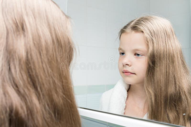 Girl in the bathroom looks in the mirror at her combed hair stock photo