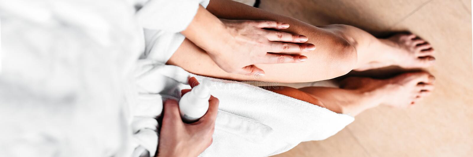 The girl in the bathroom puts anti-cellulite cream, serum on the legs and body. Body care concept. Top View. Banner stock photo