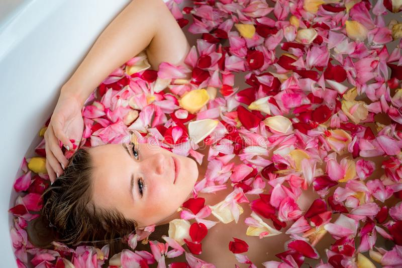 Girl in the bathroom with rose petals, close up portrait royalty free stock photo