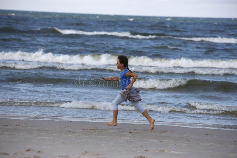 Girl on the beach. Girl running on the beach royalty free stock photo