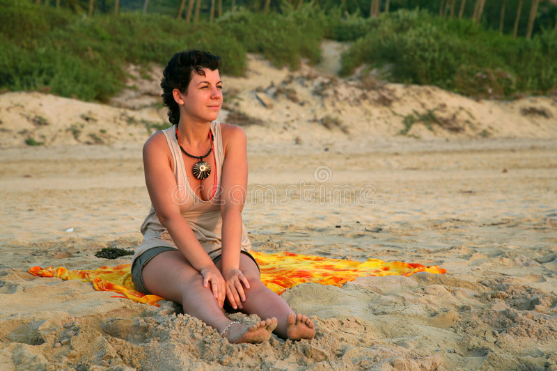 Girl on the beach. Pretty caucasian girl on the yellow sand over colorfull sunset in Goa stock images
